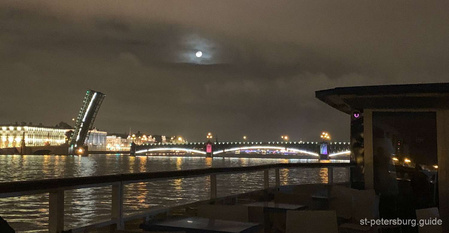 Opening of Trinity bridge, one of the drawbridges of Saint Petersburg Russia. Full moon and the city view