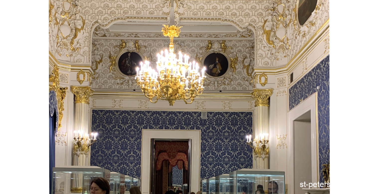 Blue hall with a grandiose golden decorations and a chandelier. Shuvalov Palace in Saint Petersburg Russia