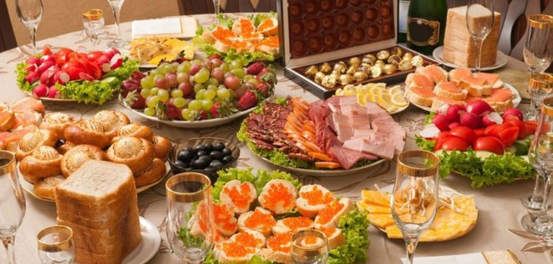 Russian New Year dinner table has many different dishes on the list