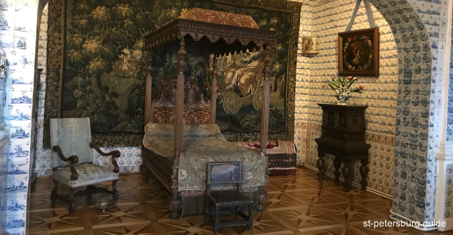 Bedroom in Meshikov Palace. Designed interior with carpets, paintings and styled furniture.