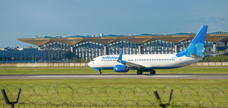 ST. PETERSBURG, RUSSIA - AUGUST 08, 2020: Boeing 737-8?? (VP-BQM) aircraft of Pobeda Airlines against the background of the new terminal building. Pulkovo Airport