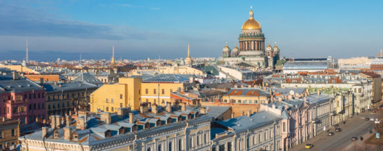 St. Isaac's Cathedral in the distance above the rooftops of the city of Saint-Petersburg, a view from the heights of the Moika River and the old urban panorama.