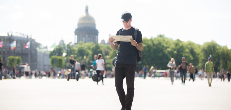 Young handsome traveler man with backpack wearing casual clothes and cap looking at map, searching for direction while walking in European city street in summer